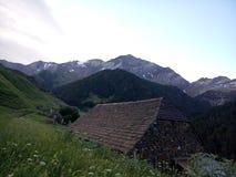 ett härligt landskap i bergen med en mycket liten koja på mitt Arkivfoton