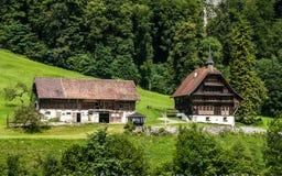 Ett härligt sommarlandskap med två trevliga hus som lokaliseras på foothillen av fjällängarna i Engelberg, Schweiz Royaltyfri Fotografi