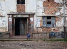 Ett hårt liv - pojke som kikar in i byggnad Harare slumkvarter Arkivfoton