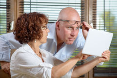 Ett högt par som i regeringsställning håller ögonen på en digital minnestavla royaltyfria foton