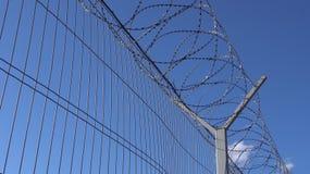 Ett högt skyddande staket med försett med en hulling - tråd royaltyfri bild