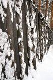 Ett högt trästaket som täckas med snö Arkivbilder
