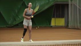 Ett högväxt och att le flickan med en handikappportion klumpa ihop sig i tennis Gladlynt och aktivt Inomhus tennisbana stock video