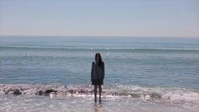 Ett hellångt skott av en härlig flicka i ett kort blöter klänninganseende i havet arkivfilmer