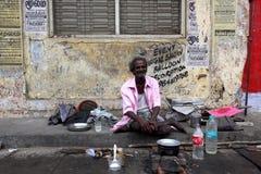 Ett hemlöst mansammanträde för eldery på gatan Med kitchenware och vatten för att laga mat använde han detta område som ett hem Royaltyfri Foto