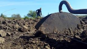 Ett hjälpmedel för att odla jorden och mannen i en hatt odlar jorden i bakgrunden arkivfilmer