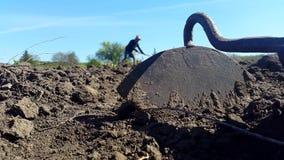 Ett hjälpmedel för att odla jorden och mannen i en hatt odlar jorden i bakgrunden lager videofilmer