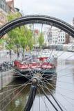 Ett hjul för cykel` s nära kanalen och några historiska byggnader Arkivbild