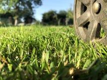 Ett hjul från en gräsklippare på en truncheted lantgårdgräsmatta arkivbild