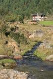 Ett hus byggdes nära en bäck nära Gangtey, Bhutan Arkivbilder