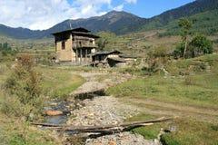 Ett hus byggdes på kanten av en bäck i bygden nära Gangtey (Bhutan) Royaltyfria Bilder