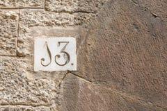 Ett hus nummer tretton & x28; 13& x29; på en vägg i Girona Royaltyfri Fotografi