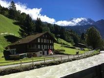 Ett hus vid sjön som omges av schweiziska fjällängar Royaltyfria Bilder