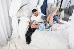 Ett incredibly gulligt par som hemma kramar i s?ng och att ha en gyckel fotografering för bildbyråer