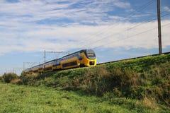 Ett intercity drev för VIRM i järnvägspår på sealevel i Nieuwerkerk den aan hålan IJssel fotografering för bildbyråer