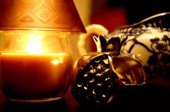 Ett intimt hörn med stearinljuset och granatäpplet Royaltyfri Foto