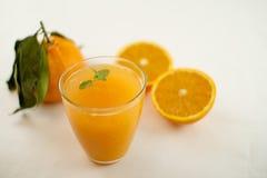 Ett inviterande exponeringsglas som är fullt av orange fruktsaft med ett blad för ny mintkaramell som svävar I bakgrunden en apel royaltyfria bilder