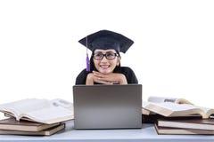 Ett isolerat skott av den lyckliga kvinnligkandidatstudien med bärbara datorn och böcker Arkivbild