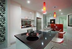 Ett kök med att äta middag tabellen och härlig röd stol Royaltyfri Foto