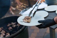 Ett kött för mandanandehöna på grillfestgaller i svarta handskar royaltyfria foton