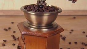 Ett kaffe maler fyllt med kaffebönor Kaffegrinder med kaffebönor I köket på marmortabellen stock video