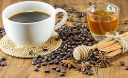 Ett kaffe på koppen med kaffebönor, honung och nolla för kanelbruna pinnar Fotografering för Bildbyråer
