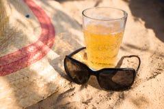 Ett kallt öl, solglasögon och en sommarhatt på stranden Koppla av semesterbegreppsbild arkivfoto