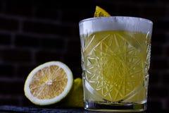 Ett klassiskt recept för surt för whisky - med bourbon, rottingsirap och citronjuice som garneras med apelsinen traditionell aper arkivbild