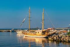 Ett klassiskt träskepp på soluppgång som anslutas i hamnen av Nessebar den forntida staden på den bulgarBlack Sea kusten ett träs arkivbilder