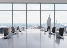 Ett konferensrum som utrustas av moderna bärbara datorer i ett modernt panorama- kontor i New York Svarta läderstolar och en vit  stock illustrationer