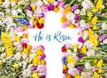 Ett kors på en färgrik blommabakgrund lekmanna- easter lägenhet Arkivfoton