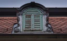 Ett kronafönster, gammalt som omges av tegelplattan royaltyfria foton