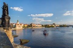 Ett kryssningskepp som ses från den Charles bron med en staty i förgrunden och staden i bakgrunden i Prague royaltyfria foton