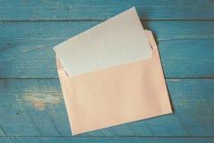 Ett kuvert på träbakgrund royaltyfria bilder