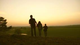 Ett kvinna-, man- och barnlopp, går i skogen, tycker om landskapet på solnedgången Handelsresandefamiljlopp med ryggsäckar lager videofilmer