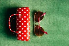 Ett kvinnligt exponeringsglasfall för röd vit prick och en rosa solglasögon arkivbild