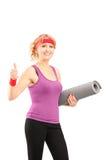 Ett kvinnligt idrottsman neninnehav för mogna ett mattt och ge en tum upp arkivbild