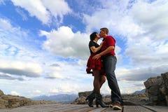 Ett kyssande par framme av en molnig himmel royaltyfri fotografi