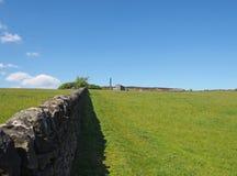 ett långt stenar väggen i perspektivet som gränsar en äng för grönt gräs i ljust vårsolljus med övergett ett historiskt, maler oc arkivfoto