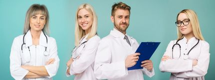 Ett lag av s?kra doktorer ser kameran och ler i studion p? en bl? bakgrund royaltyfri fotografi
