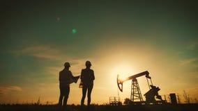 Ett lag iscensätter att diskutera underhållet av ett fält för oljapump Tekniklag som arbetar i oljeraffinaderi tv? arbetare lager videofilmer
