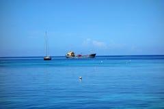 Ett lastfartyg och en seglingyacht achored i granatäppelsafterna Royaltyfria Foton