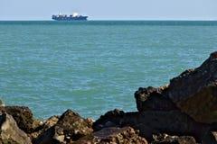 Ett lastfartyg på horisonten i det gröna havet royaltyfri fotografi