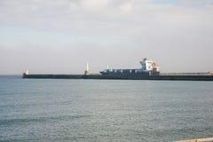 Ett lastfartyg som avgår Aberdeen port mellan två fyrar på hamningången Royaltyfri Fotografi