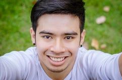 Ett le ungt asiatiskt foto för mandanandeselfie royaltyfri bild