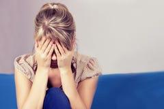 Ett ledset kvinnasammanträde på soffan och innehavet hennes huvud i henne händer royaltyfri foto