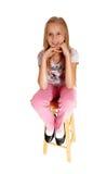 Ett ledset seende ung flickasammanträde på stol Royaltyfri Fotografi