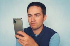 Ett ledset uttryck på framsidan av en ung man som rymmer en modern smartphone på en blå bakgrund arkivfoto