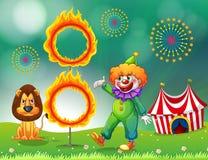 Ett lejon och en clown med en cirkel av brand Royaltyfri Foto