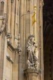 Ett lejon står vakten för den kungliga ingången nedanför det Victoria tornet på den brittiska parlamentbyggnaden i London, Englan arkivbild